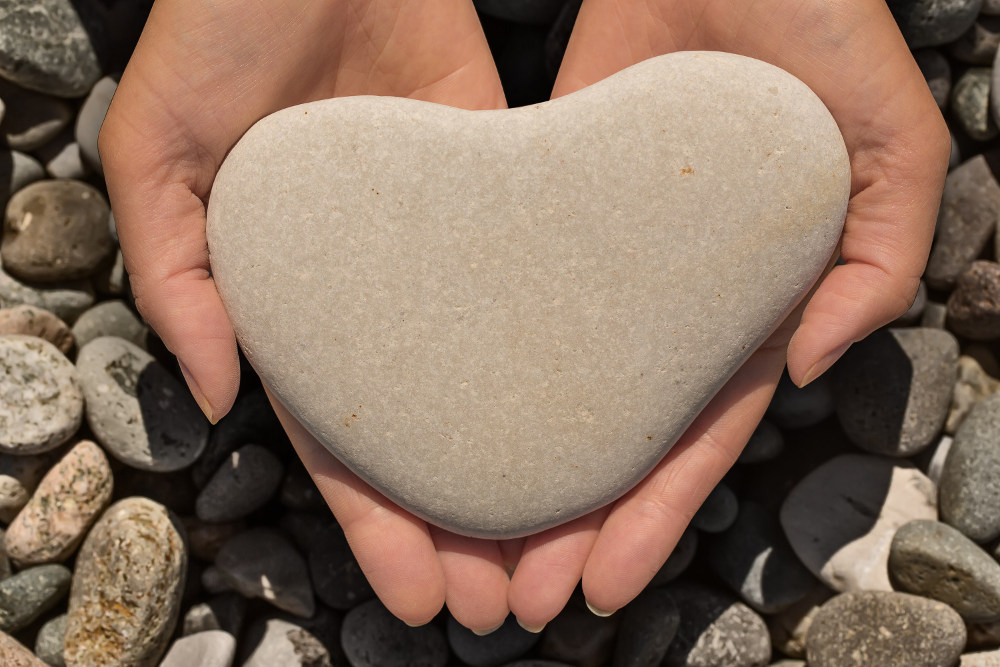 Female hands holding a natural heart-shaped stone in cupped palms over a background of water worn pebbles